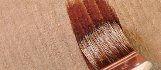 Pinsel beim aufbringen von Farbe auf grobes Holz
